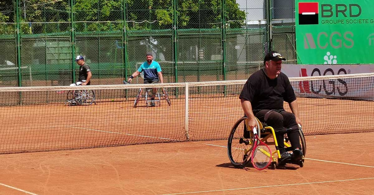 Men play wheelchair tennis in an ITF tournament