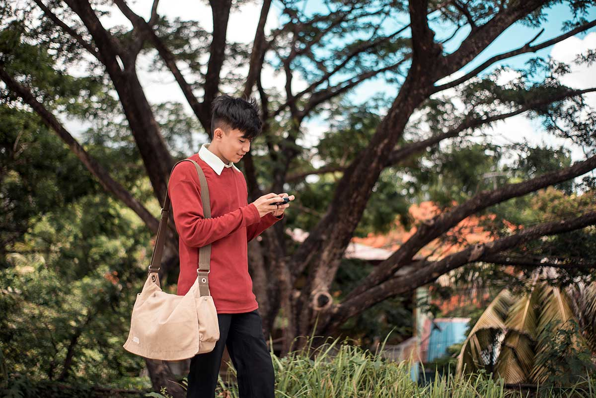 Gen Z age student walks and stares at smartphone
