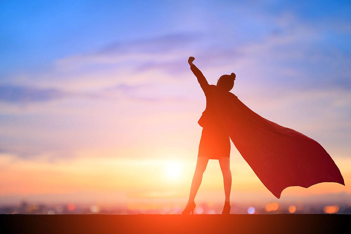 Super businesswoman in cape with triumphant pose