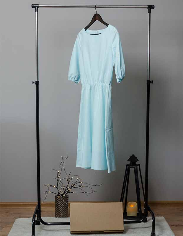 High-end dress rental hanging on a rack at home