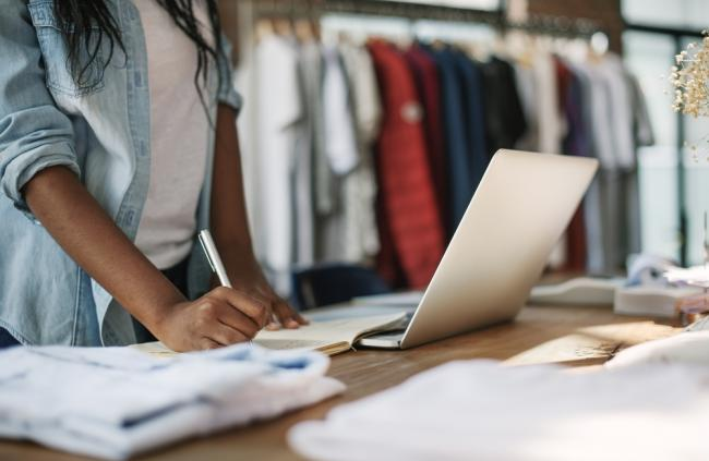 retail industry, retail store planning, designer checking clothing inventory