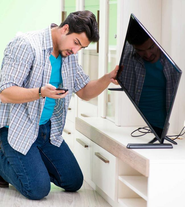 Man on smartphone to repair his television