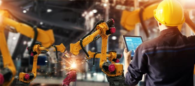 Engineer check and control welding robotics automatic arms machine in intelligent factory automotive industrial with monitoring system software.