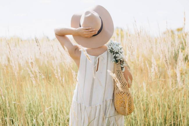 Woman wearing eco-friendly fashionable dress made of organic cotton standing in a field