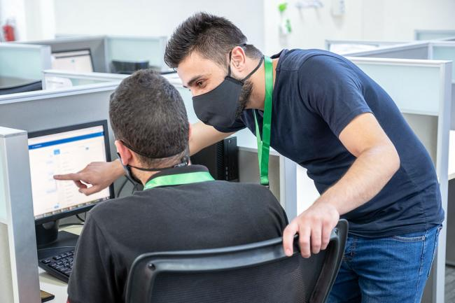 Call center trainer and employee in masks