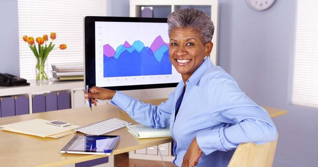 Executive at desk with tablet and computer