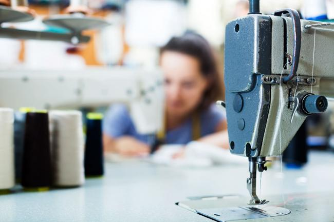 Close-up of sewing machine with seamstress in background