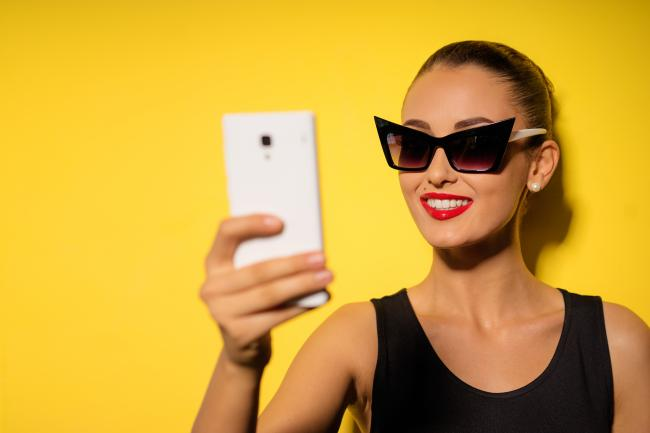 Fashionable influencer taking a selfie with her new stylish sunglasses on