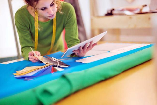 Young fashion designer works on tablet