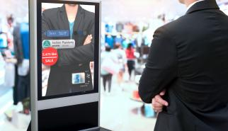 Man standing in front of an augmented reality mirror at a store showing the prices of the items he is trying on