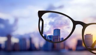 Image of eyeglasses bringing into focus a distant city